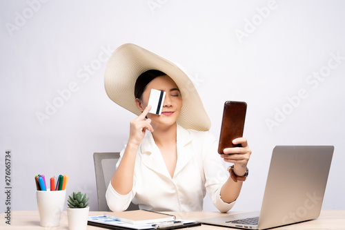 Woman wearing hat use smart phone and credit card at office isolated over backgr Canvas Print