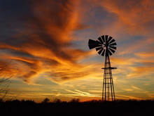 Kansas Windmill At Sunset With Colorful Clouds.