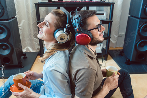 Foto op Canvas Op straat Couple with headphones enjoying music from the Hi-Fi stereo