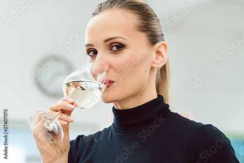 Foto op Canvas Op straat Woman drinking a glass of white wine after work
