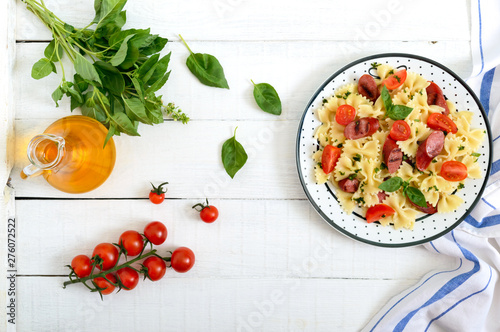 Stickers pour porte Fleur Tasty pasta farfalle with grilled sausages, fresh cherry tomatoes and basil on a plate on a white wooden background. Top view, flat lay.