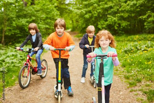 Photographie  Gruppe Kinder mit Tretroller und Fahrrad
