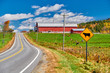 Highway and red barn at sunny autumn day in New Hampshire, USA