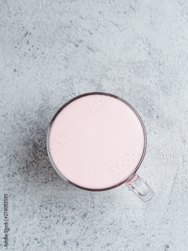 Trendy drink: pink latte. Beetroot or raspberry cappuccino or latte in glass cup on gray cement background. Copy space for text. Vertical. Top view or flat lay.