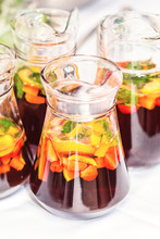 Several Pither Jugs With Traditional British Summer Pimms Cocktail Punch With Lemonade, Strawberries, Cucumber, Orange And Mint Isolated. Garden Party Refreshment Or Catering Concept With Copy Space
