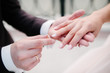 The bridegroom puts the wedding ring on the bride close up. The bride puts the bridegroom on the wedding ring.