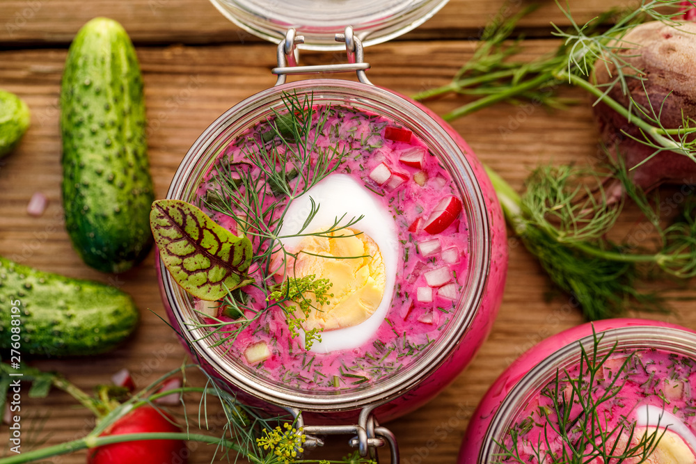 Fototapeta Cold beetroot soup, cold served with the addition of cucumbers, radishes, boiled eggs and fresh herbs, dill, green onions in glass jars on a wooden table, top view. Chilled Lithuanian cold soup
