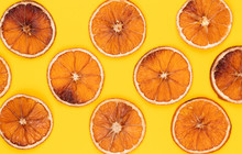 Baked Orange Slices. Pattern Of Dried Orange Slices On Yellow Background. Creative Minimal Holiday Background.