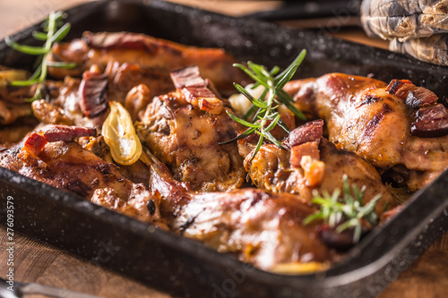 Fototapeta Portioned baked rabbit in a pan with onion rosemary and sauce obraz