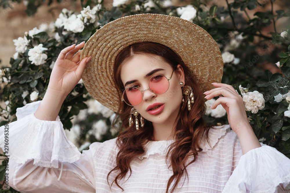Fototapety, obrazy: Outdoor close up portrait of young beautiful lady wearing pink round sunglasses, straw hat, pearl earrings, vintage white blouse. Model looking at camera, posing in the blooming rose garden