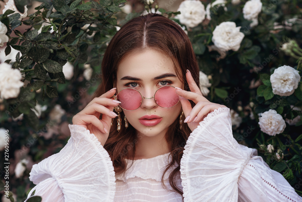 Fototapety, obrazy: Outdoor close up portrait of young beautiful lady wearing pink round sunglasses, vintage white blouse, model looking at camera, posing in the blooming roses garden