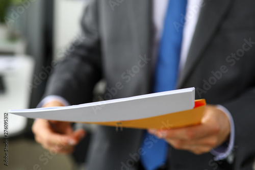 Clerk hand in suit and tie holding yellow envelope containing batch of important papers