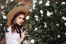 Outdoor Close Up Portrait Of Young Beautiful Lady Wearing Wide Brim Ribbon Tie Straw Hat, Pearl Earrings, Vintage White Blouse. Model Looking At Camera, Posing In The Blooming Rose Garden. Copy Space