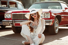 Full-length Street Fashion Portrait Of Young Elegant Luxury Lady Wearing White Sunglasses, Wide Brim Hat, Striped Linen Jumpsuit, Holding Animal Print Zebra Purse, Posing Near Red Car. Copy Space