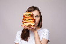 Studio Portrait Of Young Brunette Woman In White T-shirt Holding Enormous Burgers On Her Hand Looking Shocked Or Surprised At Camera.