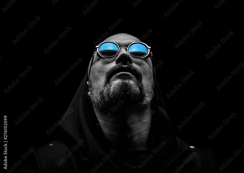 Fototapeta Bald man with a gray beard in sunglasses on a dark background. The concept of hope.