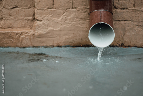 Valokuva  Rainwater flows out of the drainpipe