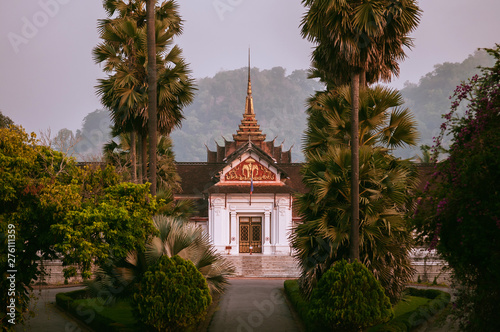 Con. Antique Luang Prabang Royal Palace Museum among palm tree in morning