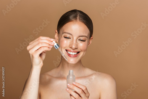 Garden Poster Spa Smiling happy young amazing woman posing isolated over brown chocolate background wall holding oil drop serum.