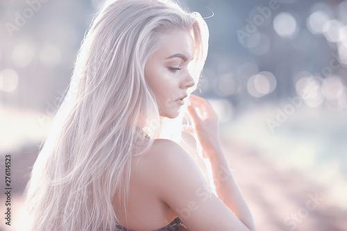 Photo Stands Height scale blonde long hair nature summer / happy adult girl with developing in the wind long blonde hair in the summer field