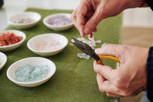 Close-up Image Of Creative Woman Using Pliers To Put Semi-precious Stones On Elastic Cord