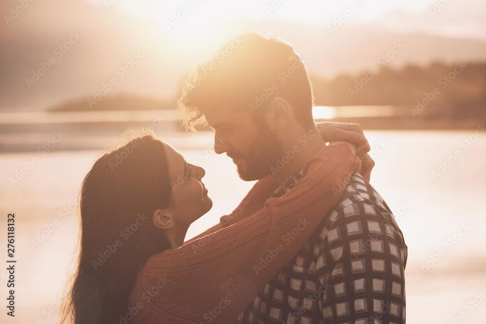 Fototapeta Romantic loving couple kissing at sunset