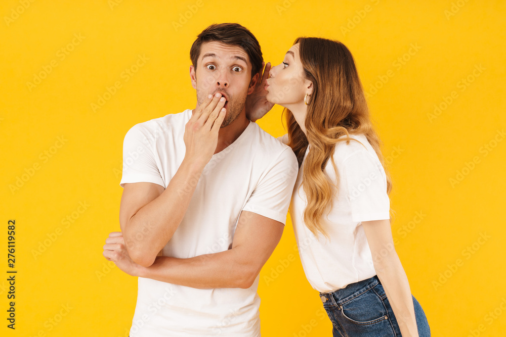 Fototapeta Portrait of young woman whispering secret or interesting gossip to excited man in his ear