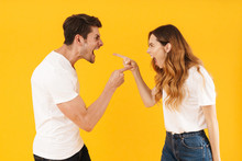 Photo Of Irritated Aggressive Couple Man And Woman In Basic T-shirts Screaming At Each Other While Standing Face To Face