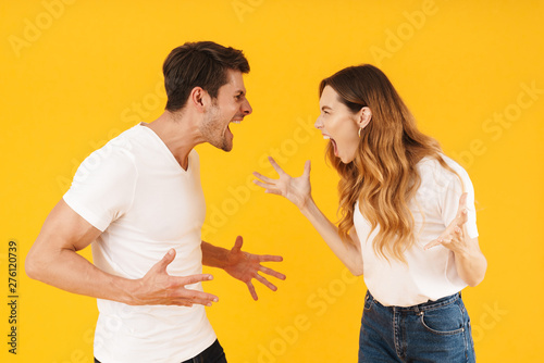 Photo Photo of furious aggressive couple man and woman in basic t-shirts screaming at
