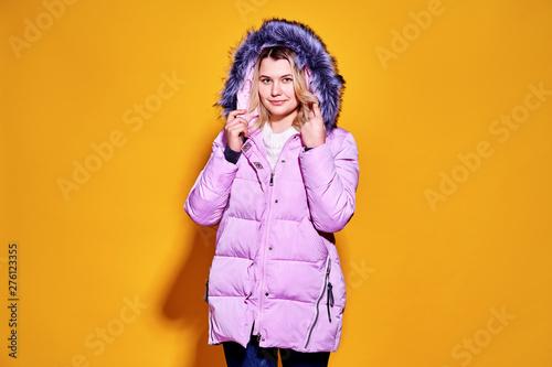 Young fashion woman in short violet down jacket. Fototapeta