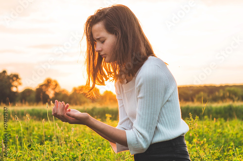 Fotografija Teenager Girl closed her eyes, praying in a field during beautiful sunset