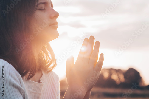 Teenager Girl closed her eyes, praying in a field during beautiful sunset Fototapet