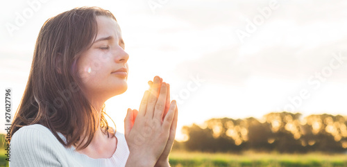 Fotografie, Tablou Teenager Girl closed her eyes, praying in a field during beautiful sunset