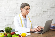 Focused Middle Aged Woman Nutritionist Studying Public Health Scientific Research On Food To Treat Nutritional Problems, Sitting At Desk With Various Vegetables, Keyboarding On Portable Computer