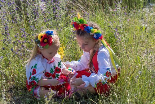Valokuva Sisters in traditional Ukrainian costumes playing in the spring countryside