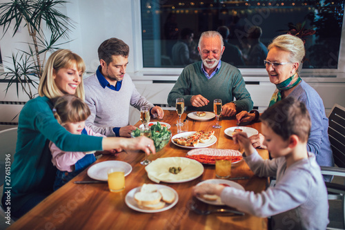 Poster Affiche vintage Multi generation family enjoying meal around table at home
