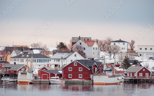 Taupe Norwegian village with fishing boat on coastline in winter