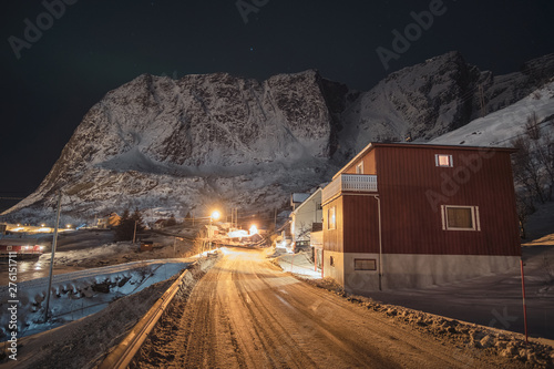 Norwegian village on country road with light shining and snow mountain range