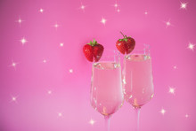 Two Glasses Of Champagne And Fresh Strawberry On Pink Background. Selective Focus.
