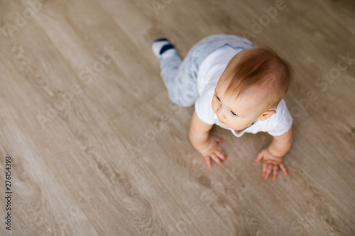 Obraz Cute little baby boy lying on hardwood and smiling. Child crawling over wooden parquet and looking up with happy face. View from above. Copyspace - fototapety do salonu