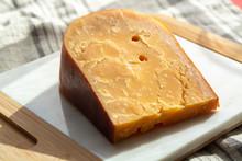 Three Years Old Dark Yellow Hard Dutch Cheese In Sun Lights