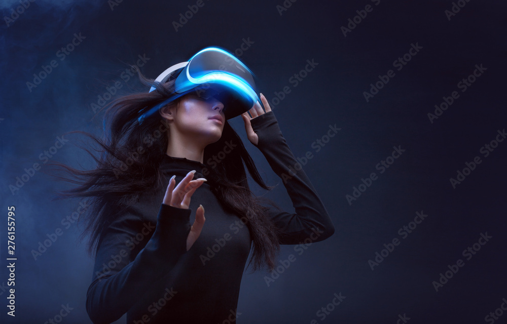 Fototapeta Beautiful woman with flowing hair in futuristic dress over dark background. Girl in glasses of virtual reality. Augmented reality, science, future technology, robots and people concept. VR.