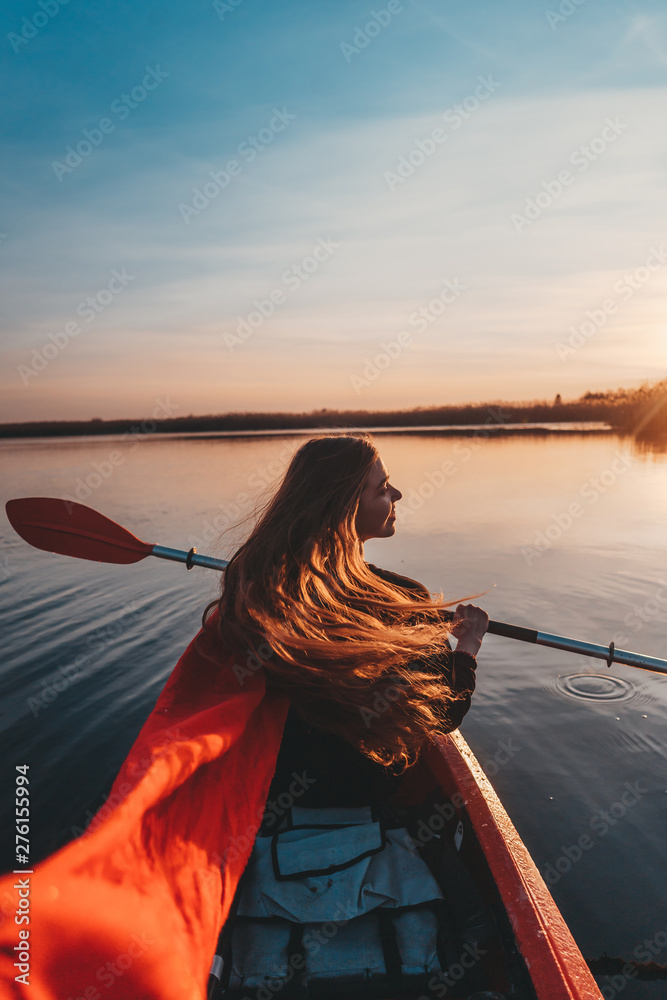Fototapety, obrazy: Back view of happy cute girl holding paddle in a kayak on the river