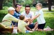 Leinwandbild Motiv Happy family playing and enjoying picnic with children outside