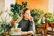Young Beautiful Woman Relaxing On Cozy Balcony, Reading A Book, Wearing Warm Knitted Pullover, Cup Of Tea Or Coffee On Stack Of Books