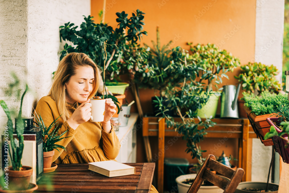 Fototapety, obrazy: Young beautiful woman relaxing on cozy balcony, reading a book, wearing brown cotton dress, holding cup of tea or coffee