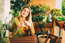 Romantic Portrait Of Beautiful Young Woman Wearing Brown Cotton Dress, Relaxing On The Balcony Between Many Green Plants, Holding Cup Of Tea Or Coffee