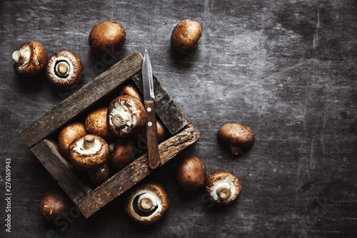Foto  Royal mushrooms on a black background with a vintage board and a kitchen towel