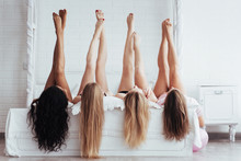 Different Skin Colors. Four Young Women With Good Body Shape Lying On The Bed With Their Legs Up