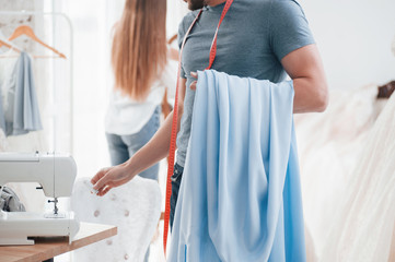 Guy takes needed tools and material. The process of fitting the dress in the studio of hand crafted clothes
